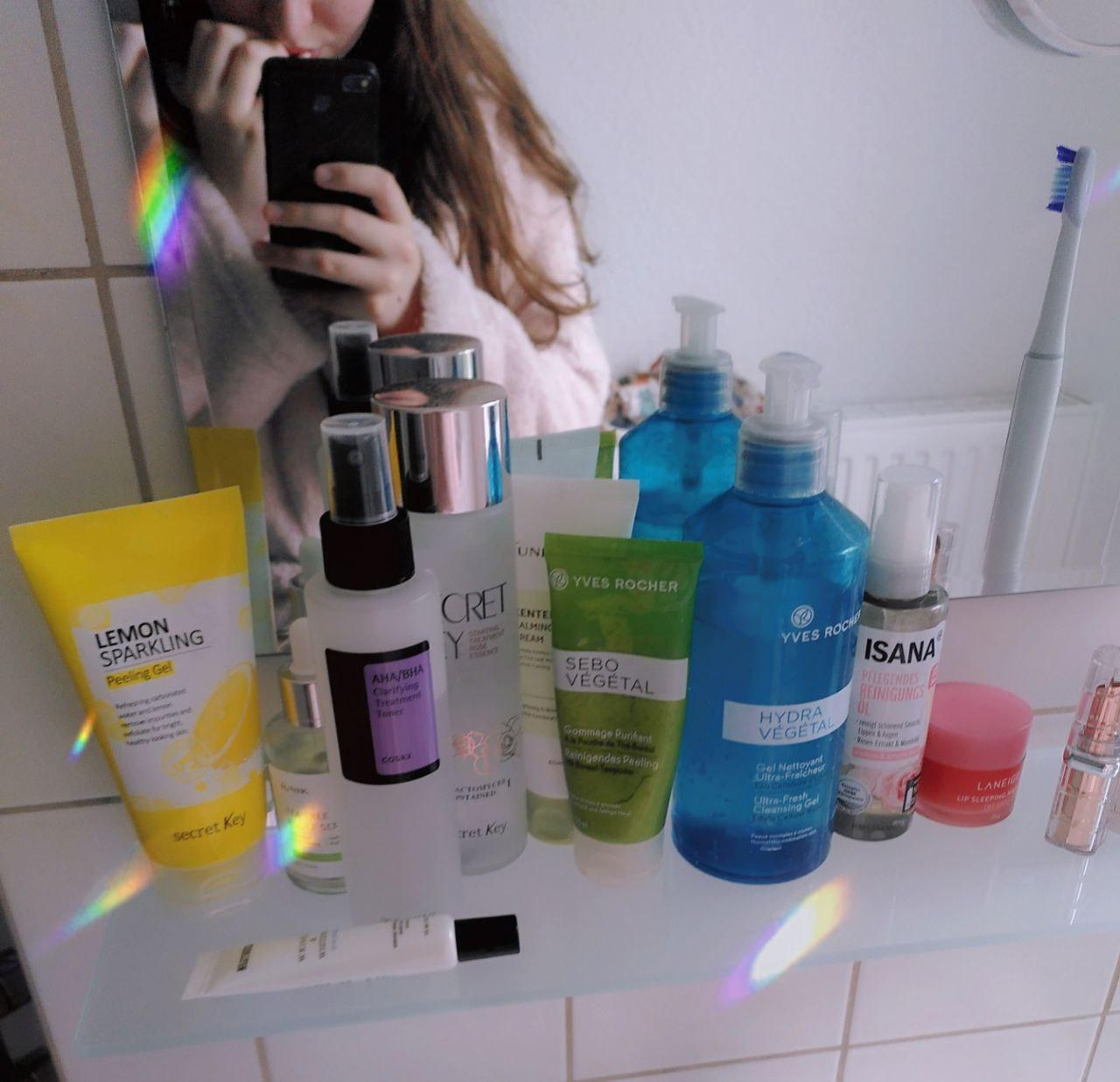 Photo by me, my skincare products on a board under the mirror in the bathroom